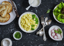Ingredients for breakfast toast - egg's scramble, toasted bread, radishes, green peas. On a dark stone background. Delicious healthy food Stock Images