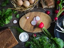 Ingredients for breakfast on wooden table. Ingredients for breakfast - fresh eggs in a wire basket, fresh greens - spinach, dill and green onions, radish, salt Stock Image