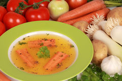 Ingredients for a broth. On a table there is a bowl of broth with ingredients such as carrots, onions, garlic royalty free stock image