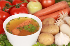 Ingredients for a broth. On a table there is a bowl of broth with ingredients such as carrots, onions, garlic royalty free stock photo