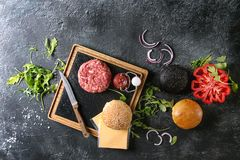 Ingredients for burger. Ingredients for cooking hamburger. Meat beef burger board, cheese, ketchup sauce, tomato, black and white buns, arugula salad over dark Stock Photo