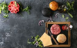 Ingredients for burger. Ingredients for cooking hamburger. Meat beef burger board, cheese, ketchup sauce, tomato, black and white buns, arugula salad over dark Royalty Free Stock Photo