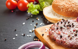 The ingredients for the burger. The raw ingredients for the homemade burger on black slate background Royalty Free Stock Photography