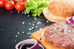 The ingredients for the burger. The raw ingredients for the homemade burger on black slate background Royalty Free Stock Photo
