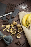 Ingredients for a cake. A wooden table with some ingredients ready for making a cake: chocolate, walnuts and banana Stock Photography