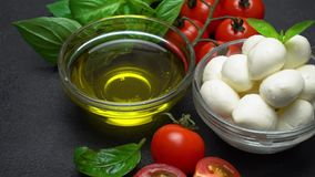 Ingredients for caprese salad - Mozzarella, tomatoes, basil leaves, olive oil. Video of Ingredients for italian caprese salad - Mozzarella balls, tomatoes, basil stock video footage