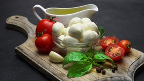 Ingredients for caprese salad - Mozzarella, tomatoes, basil leaves, olive oil. Video of Ingredients for italian caprese salad - Mozzarella balls, tomatoes, basil stock footage