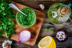 Ingredients for chimichurri sauce: fresh parsley, red onion, garlic, olive oil, lemon. On a wooden background stock image