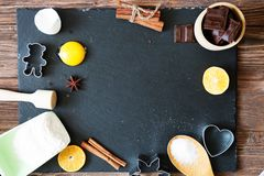 Ingredients for Christmas, winter baking cookies. Flour, cranberries, dried oranges, cinnamon, spices on a black stone table, top stock photography