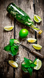 The ingredients for the cocktail - limes, mint, knife, is also prepared cocktail in the bottle and in the glass. Royalty Free Stock Image