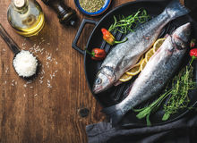Ingredients for cookig healthy fish dinner. Raw uncooked seabass  with rice, olive oil, lemon slices, herbs and spices Royalty Free Stock Photos