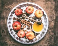 Ingredients for cooking apples with honey and nuts, cinnamon and seasonings, sliced apples with filling on a rustic wooden backgro royalty free stock photos
