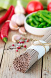 Ingredients for cooking buckwheat noodles with vegetables - dry raw buckwheat noodles, red peppers, green beans, garlic, tomatoes Royalty Free Stock Photos