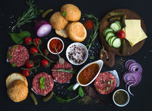 Ingredients for cooking burgers. Raw ground beef meat cutlets, buns, red onion, cherry tomatoes, greens, pickles, tomato Royalty Free Stock Image