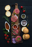 Ingredients for cooking burgers. Raw ground beef meat cutlets on wooden board, red onion, cherry tomatoes, greens Stock Images