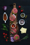 Ingredients for cooking burgers. Raw ground beef meat cutlets on wooden chopping board, red onion, cherry tomatoes. Greens, pickles, tomato sauce, cheese Royalty Free Stock Image