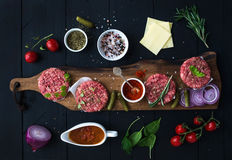 Ingredients for cooking burgers. Raw ground beef meat cutlets on wooden chopping board, red onion, cherry tomatoes. Greens, pickles, tomato sauce, cheese Stock Photos
