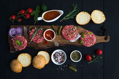Ingredients for cooking burgers. Raw ground beef meat cutlets on wooden chopping board, red onion, cherry tomatoes. Greens, pickles, tomato sauce, cheese Royalty Free Stock Photography