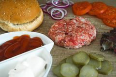 Ingredients for cooking burgers. Raw ground meat cutlets on wooden background, red onion, tomatoes, greens, pickles, tomato s Stock Photography