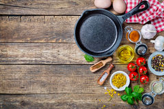 Ingredients for cooking and cast iron skillet. On an old wooden table. Food background concept with copyspace Royalty Free Stock Photography