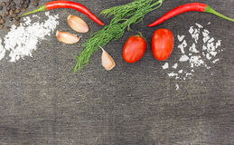 Ingredients for cooking (cherry tomatoes, fresh dill weed, garlic, salt, black pepper) on dark wooden background royalty free stock photos