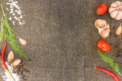 Ingredients for cooking (cherry tomatoes, fresh dill weed, garlic, salt, black pepper) on dark wooden background royalty free stock photography