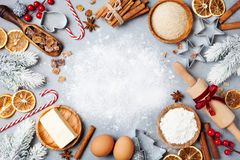 Ingredients for cooking christmas baking decorated with fir tree. Flour, brown sugar, eggs and spices top view. Bakery background. royalty free stock images