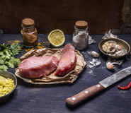 Ingredients for cooking concept Preparation of two steak  of turkey lemon herb seasoning garlic hot red pepper and knife wooden Stock Images