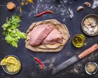 Ingredients for cooking concept Two steak of turkey with different spices lemon grass oil peeled garlic a knife on rustic wood Stock Images