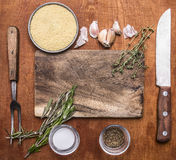 Ingredients for cooking couscous herbs cutting board garlic salt pepper old knife and fork on rustic wooden background top view cl Stock Photo