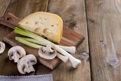 Ingredients for cooking dinner. Dutch cheese and champignon mushrooms. Fresh green onions. On a board and a wooden background. Free space for text Royalty Free Stock Photography