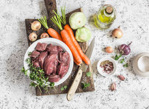 Ingredients for cooking dinner - raw beef meat, carrots, squashes, onions, garlic, thyme, spices, olive oil. On a light background Stock Images
