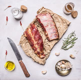 Ingredients for cooking double  raw lamb ribs on paper with a knife, garlic, salt, butter and herbs on white wooden rustic backgro Stock Images