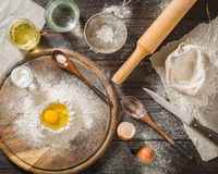 Ingredients for cooking dough or bread. Broken egg on top of a bunch of white rye flour. Dark wooden background. Stock Photos