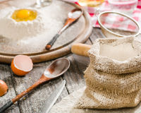 Ingredients for cooking dough or bread. Broken egg on top of a bunch of white rye flour. Dark wooden background. Royalty Free Stock Images