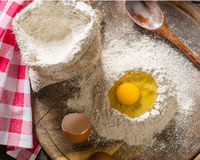 Ingredients for cooking dough or bread. Broken egg on top of a bunch of white rye flour. Dark wooden background. Royalty Free Stock Photo