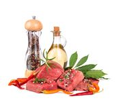 Ingredients for cooking. Fresh raw beef meat slices with bay leaves, olive oil and pepper mill isolated over white background Royalty Free Stock Photos