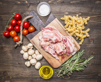 Ingredients for cooking fusilli pasta with bacon vegetables, spices and herbs on a cutting board on wooden rustic background top v Stock Photos