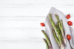 Ingredients for cooking healthy breakfast: fresh asparagus, tomatoes on white table. Rustic style composition. Flat lay, top view stock images