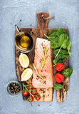 Ingredients for cooking healthy dinner. Raw salmon fillet, spinach, tomatoes, olive oil, lemon, peppers, rosemary and Stock Photo