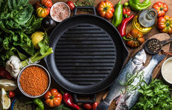 Ingredients for cooking healthy dinner. Raw uncooked seabass fish with vegetables, grains, herbs and spices over rustic Royalty Free Stock Images