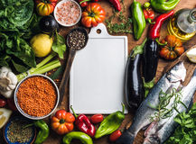 Ingredients for cooking healthy dinner. Raw uncooked seabass fish with vegetables, grains, herbs and spices over rustic Stock Photos