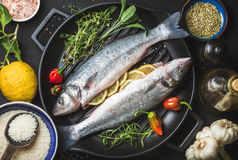 Ingredients for cooking healthy fish dinner. Raw uncooked seabass with rice, lemon, herbs and spices on black grilling Stock Photography