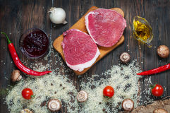 Ingredients for cooking healthy meat dinner. Raw uncooked beef rib eye steaks with mushrooms, rice, herbs and spices on table back royalty free stock image