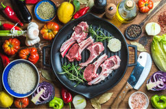 Ingredients for cooking healthy meat dinner. Raw uncooked lamb chops in iron grill pan with vegetables, rice, herbs and Stock Image