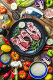 Ingredients for cooking healthy meat dinner. Raw uncooked lamb chops in iron grill pan with vegetables, rice, herbs and Stock Photo