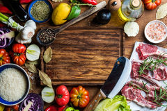 Ingredients for cooking healthy meat dinner. Raw uncooked lamb chops with vegetables, rice, herbs and spices over rustic. Wooden background, dark chopping board Royalty Free Stock Photos