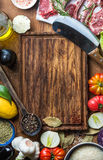 Ingredients for cooking healthy meat dinner. Raw uncooked lamb chops with vegetables, rice, herbs and spices over rustic Stock Image