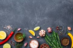 Ingredients for cooking. Herbs and spices on black stone table top view. Food background.