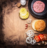 Ingredients for cooking homemade burger, tomatoes, onion rings, burger buns border ,place for text on wooden rustic background top. Ingredients  cooking homemade Royalty Free Stock Photography